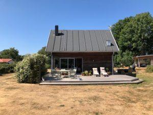 Holzhaus, umgeben vom Garten mit großer Terrasse inklusive Mobiliar. Rechts im Bild das Gästehaus