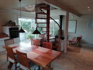 großzügig und hell eingerichtete Wohn-und Essküche mit großem Holztisch, Sofa, Kamin